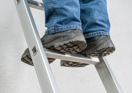 A man stands on a ladder Stockfoto