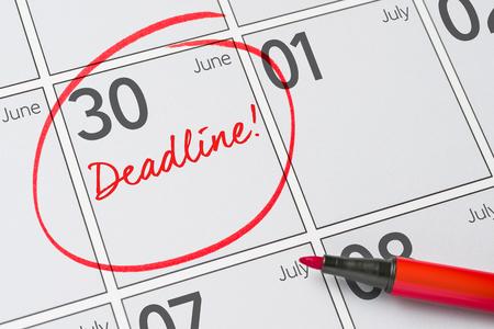 Deadline written on a calendar - June 30 Foto de archivo