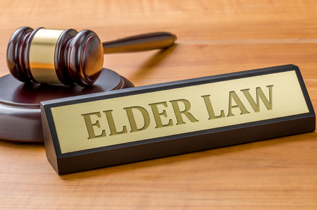 Un martillo y una placa con el grabado de la Ley de Ancianos Foto de archivo - 85752784
