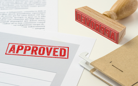 A red stamp on a document - Approved Stock Photo