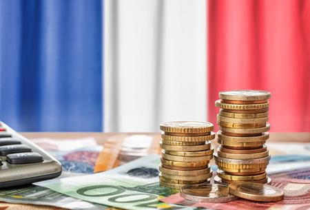 Banconote e monete in euro davanti alla bandiera nazionale della Francia Archivio Fotografico