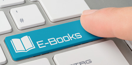 A keyboard with a blue labeled button - E-Books Foto de archivo