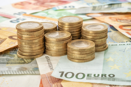 Stacks of coins with euro  bills Stock Photo