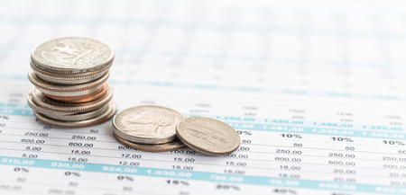 Stack of coins on a document with copy space