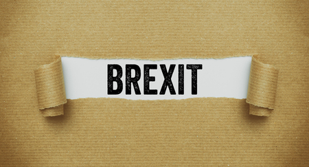 Torn brown paper revealing the word Brexit