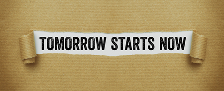 Torn brown paper revealing the words Tomorrow starts now Stock Photo