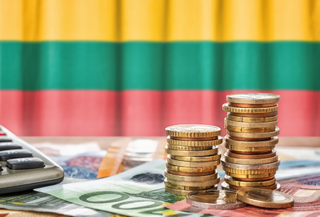 Euro banknotes and coins in front of the national flag of Lithuania Stock Photo
