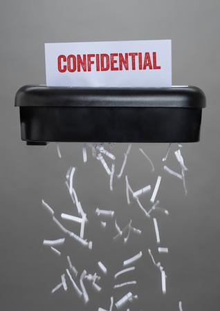 Ein Aktenvernichter zerstört ein Dokument - Vertraulich Standard-Bild