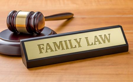 Un marteau et une plaque nominative avec la gravure Droit de la famille