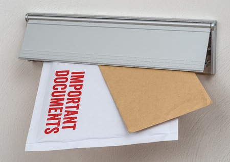 A letter labeled Important documents in a mail slot Фото со стока