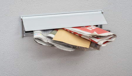 Newspapers and a letter in a mail slot Stockfoto