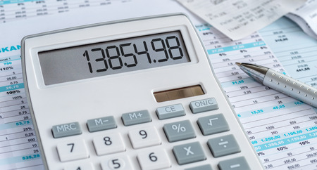 A calculator with a pen and some documents