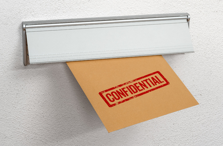 A letter stamped confidential in a mail slot