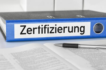 A blue folder with the label Certification - Zertifizierung (German) Archivio Fotografico