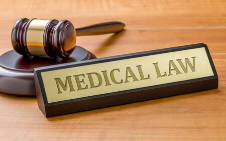 A gavel and a name plate with the engraving Medical law 스톡 콘텐츠