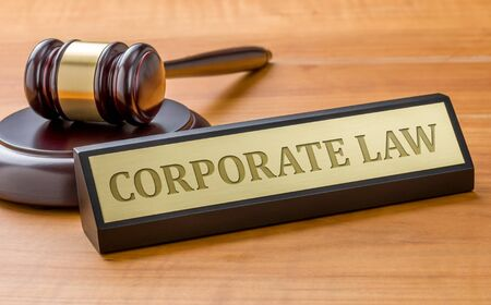 A gavel and a name plate with the engraving Corporate law Stock fotó