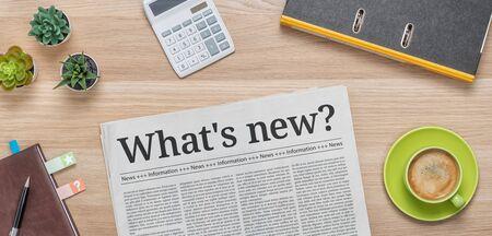 Een krant op een bureau met de kop Whats new