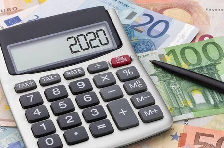 Calculator with money and a pen - 2020 Banco de Imagens