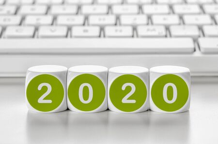 Letter dice in front of a keyboard - 2020 Stock Photo
