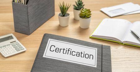 A folder on a desk with the label Certification Banco de Imagens