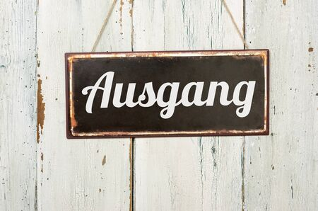 Old metal sign in front of a white wooden wall - Ausgang - German word for Exit Banco de Imagens
