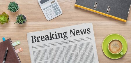 A newspaper on a desk with the headline Breaking News Banco de Imagens