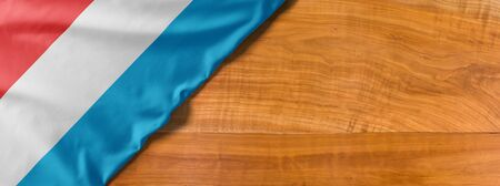 National flag of Luxembourg on a wooden background with copy space