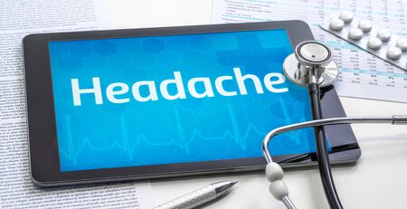 The word Headache on the display of a tablet