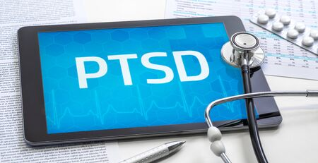 The word PTSD on the display of a tablet