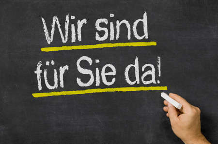 We are there for you written on a blackboard in german - We are there for you Banco de Imagens