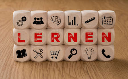 Dice with icons and the word Learn in german - Lern Reklamní fotografie