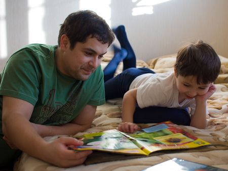 blessedness: Son with Father reading a book Stock Photo