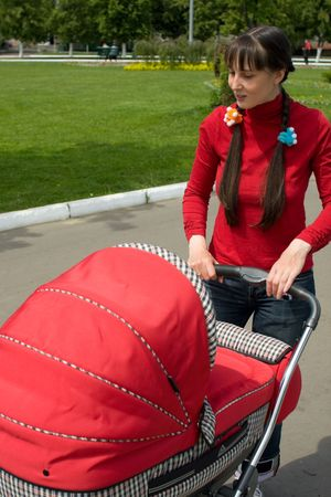 blessedness: Young woman with red baby carriage Stock Photo