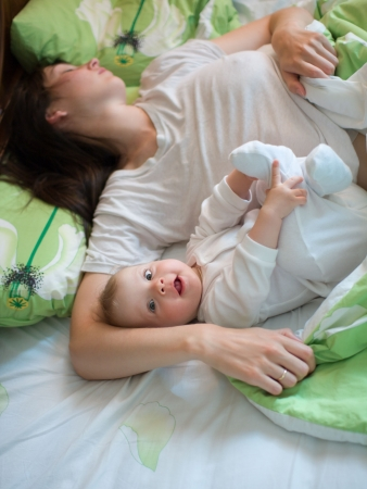 blessedness: Awake baby with sleeping mom in a bed
