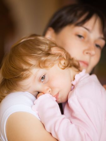composure: Sleepy little child with mom - shallow DOF, focus on little girls eyes Stock Photo
