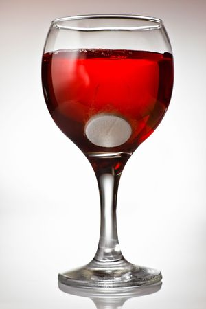Medicine and alcohol - Fizzy tablet in a goblet of red wine photo