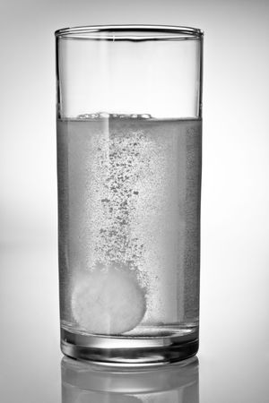 Fizzy tablet in a glass of water photo