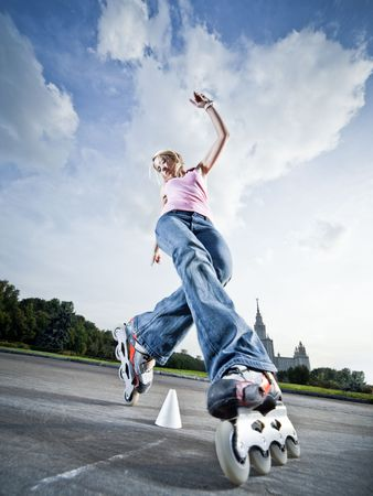 Wide-angle shot of a rollerblading girl performing compass element - little motion blur photo
