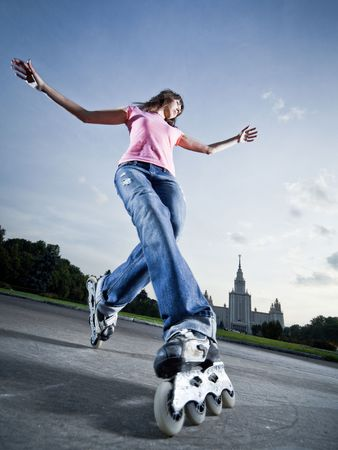 inline skates: Wide-angle shot of a rollerblading girl performing compass element - little motion blur Stock Photo