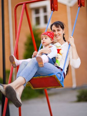 shallow dof: Little girl with mom on a swing - shallow DOF Stock Photo