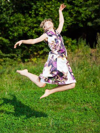 Woman jumping barefoot on green grass background - shallow DOF Stock Photo - 5811794