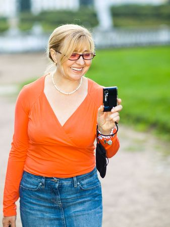 blessedness: Smiling woman with a compact photo camera - shallow DOF