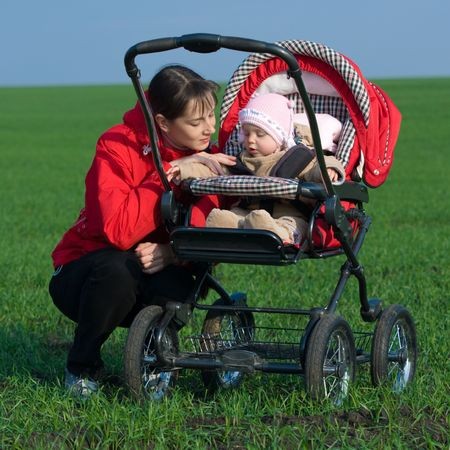 Woman in red jacket with baby buggy outdoors photo