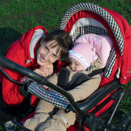 blessedness: Woman in red jacket with baby buggy outdoors