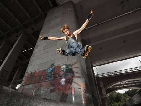 exertion: Wide angle shot of a jumping rollerskater on a dark urban background - with just a little motion blur