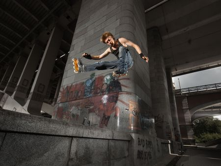 Wide angle shot of a jumping rollerskater on a dark urban background - with just a little motion blur photo