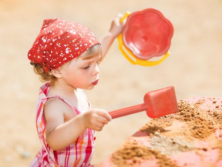Little girl playing outdoors - shallow DOF photo