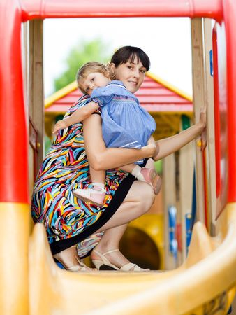 Little girl with her mom on a playground - shallow DOF photo