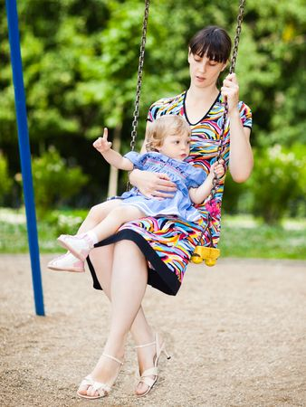 Little girl with her mom on a swing - shallow DOF photo
