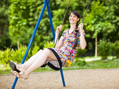 blessedness: Young lady in a short colorful dress on a swing - shallow DOF